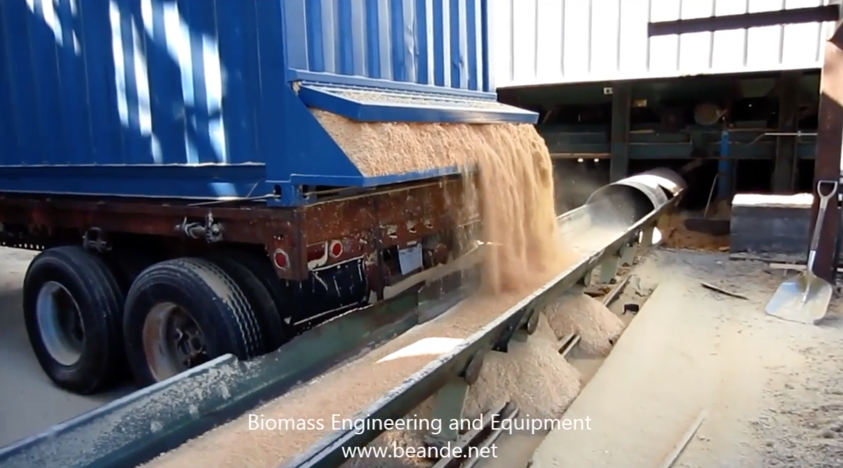 video of walking floor trailer in action, also called a live floor trailer; a horizontal silo metering out sawdust at a sawmill for biomass boiler fuel