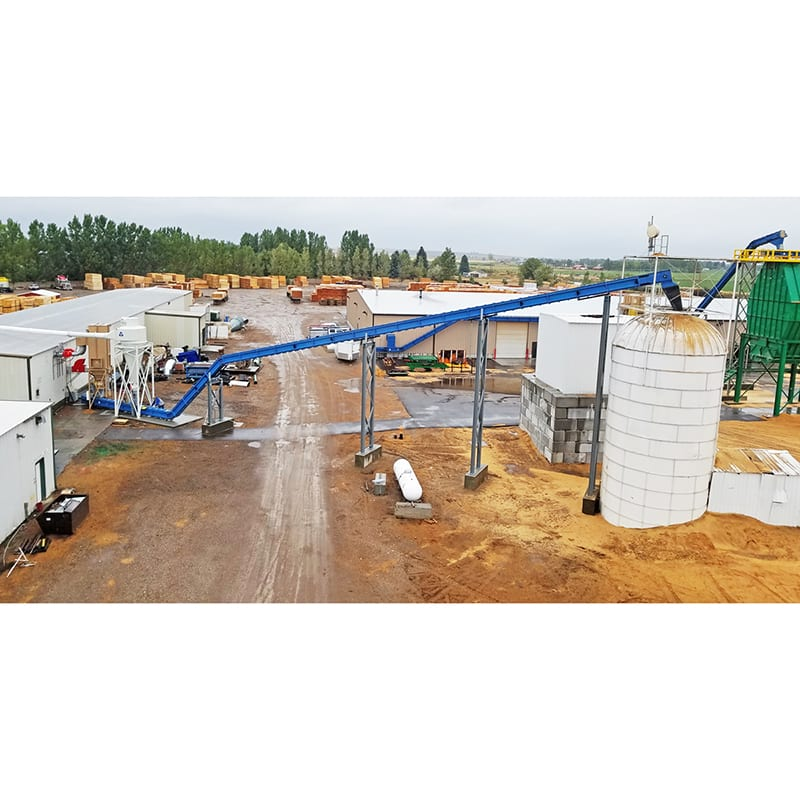 Drag chain conveyor to silo at pallet recycler - automated material handling equipment.